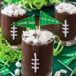 These football pudding cups are so cute for game day! Jazz them up with some white football stitches, chocolate curls, and a mini pennant!