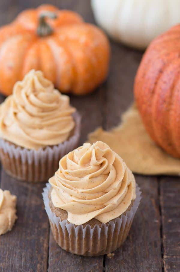 pumpkin cupcake with pumpkin frosting on wooden background with pumpkins in background