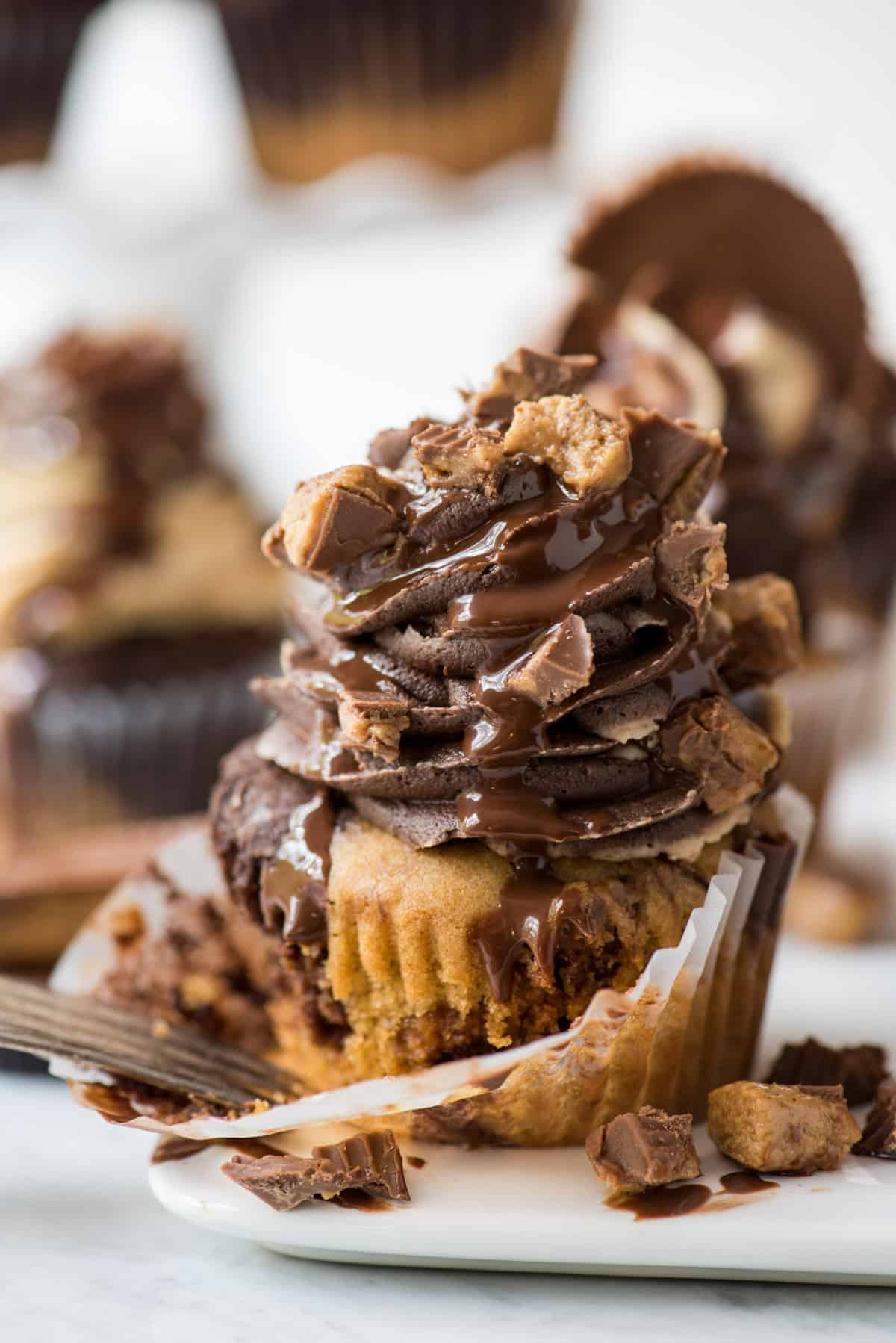 chocolate peanut butter cupcake with swirled chocolate peanut butter frosting topped with chopped reese's and drizzled with chocolate sauce on white background