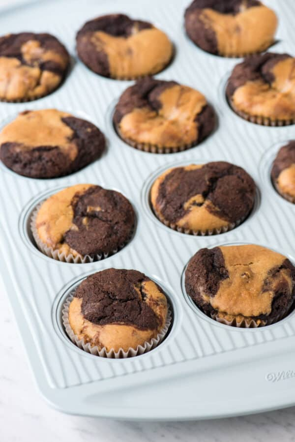 unfrosted chocolate peanut butter cupcakes in blue muffin pan