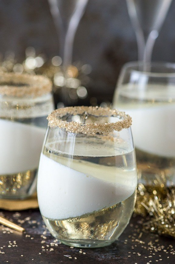champagne jello cup shots with gold sprinkles on the glass rim on dark background