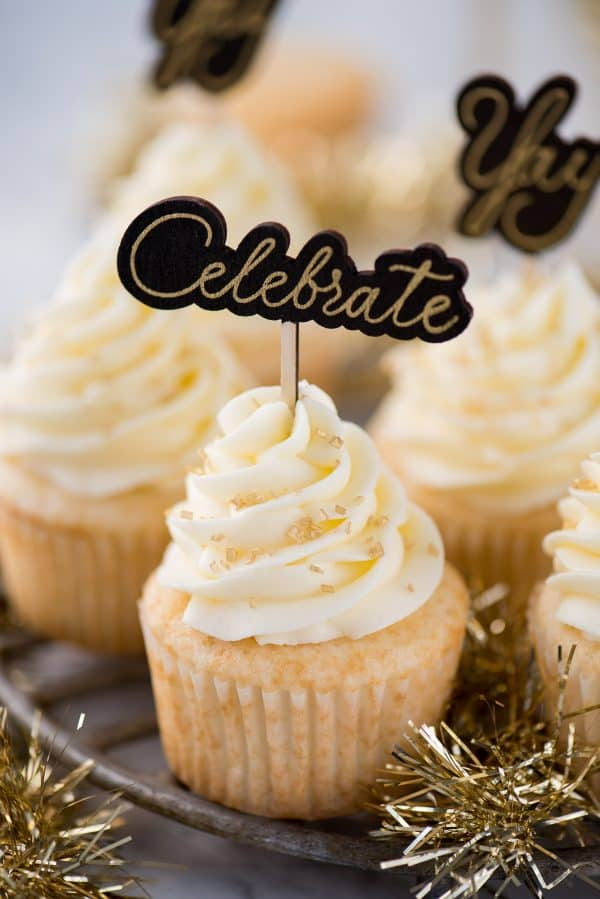 "easy champagne cupcakes with champagne buttercream topped with gold sprinkles and a cupcake topper that says ""celebrate"""