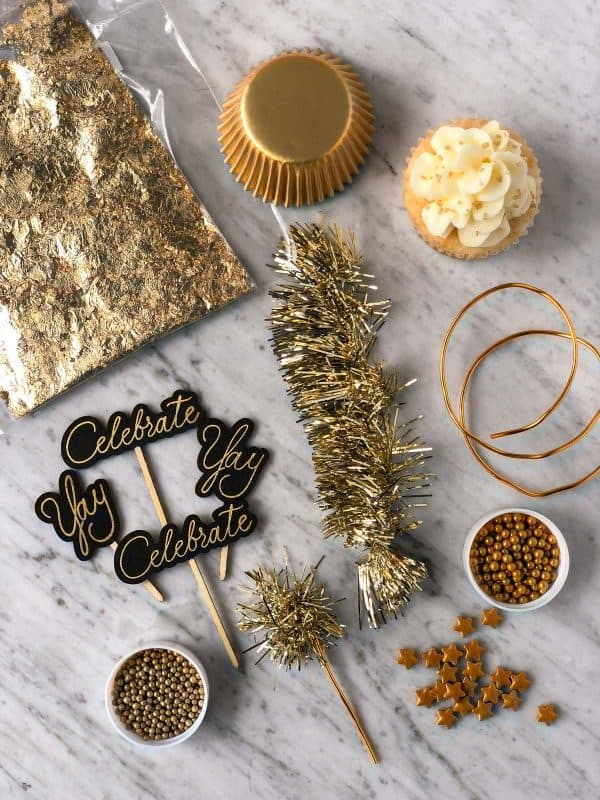 supplies used to decorate new year's eve cupcakes including gold sprinkles, gold stars, gold muffin liners, edible gold leaf, celebrate cupcake toppers, and gold tinsel