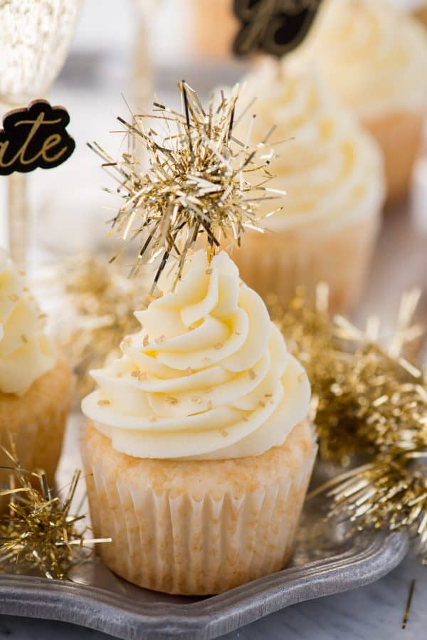 easy champagne cupcakes with champagne buttercream topped with gold sprinkles and a gold tinsel cupcake topper