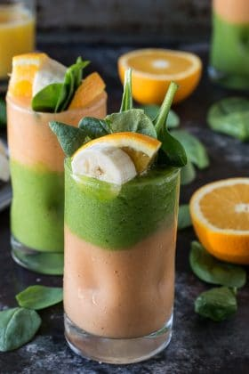 Two layer green monster orange smoothie - healthy and easy to make! Top the smoothie with a fruit skewer.