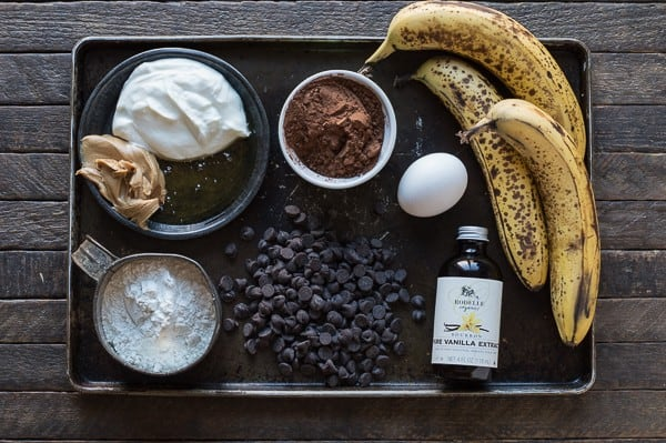 tray with baking ingredients - bananas, yogurt, peanut butter, flour, chocolate chips, egg
