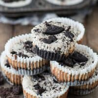 Seven mini oreo cheesecake recipe made in a muffin pan on a wooden table.