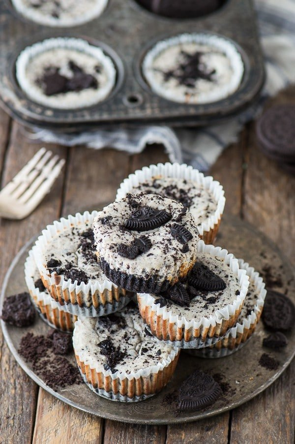 7 ingredient mini oreo cheesecake recipe on a baking sheet surrounded by broken oreos on a wooden table.