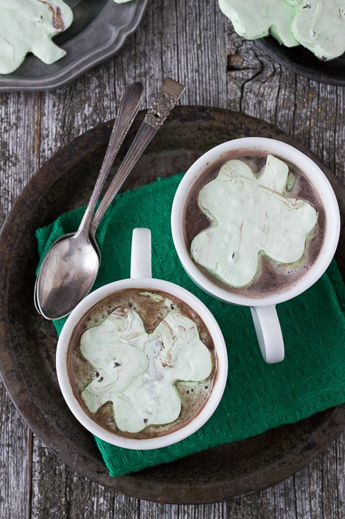 Two white mugs with Mint Chocolate Chip Shamrock Marshmallows in hot cocoa.
