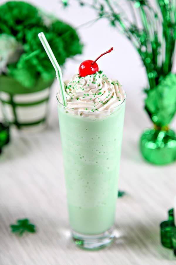 Homemade Shamrock Shake in a clear glass cup with a cherry on top and a white and green straw.