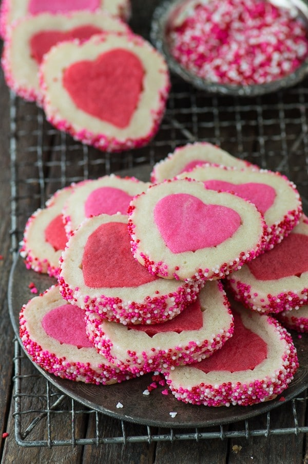 Stack of delicious Homemade Valentine's Day cookies on a cooling rack next to a bowl of pink and white sprinkles.
