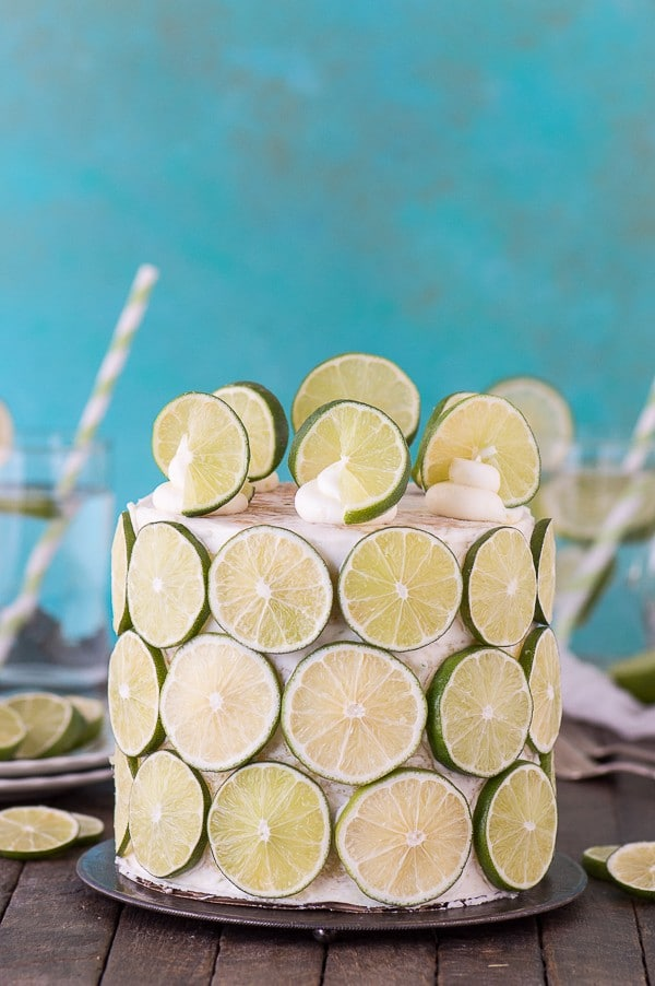 Coconut Lime Cake covered in sliced lime on a cake platter on a wooden table.