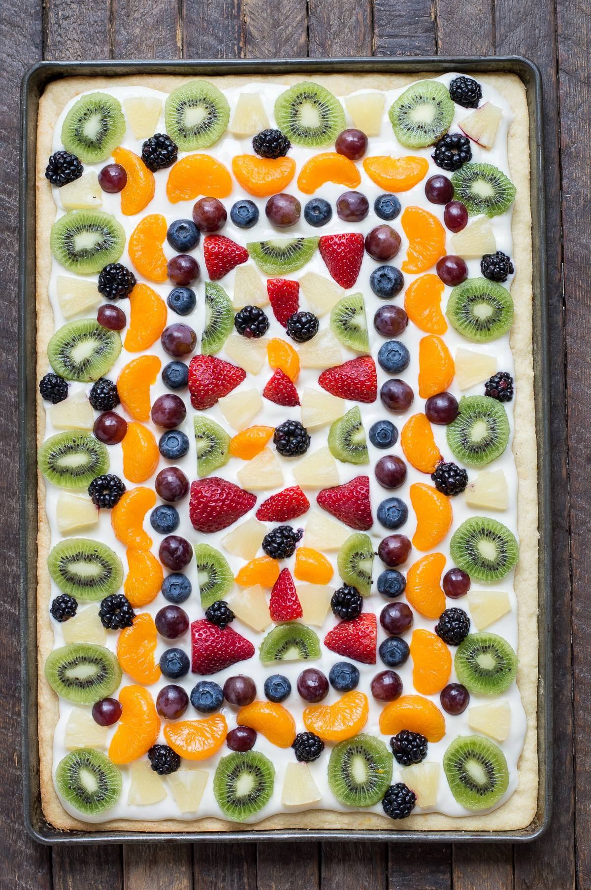 Easy fruit pizza recipe on a soft sugar cookie crust! A traditional cream cheese topping loaded with your favorite fresh fruit! Perfect fruit pizza for a crowd!