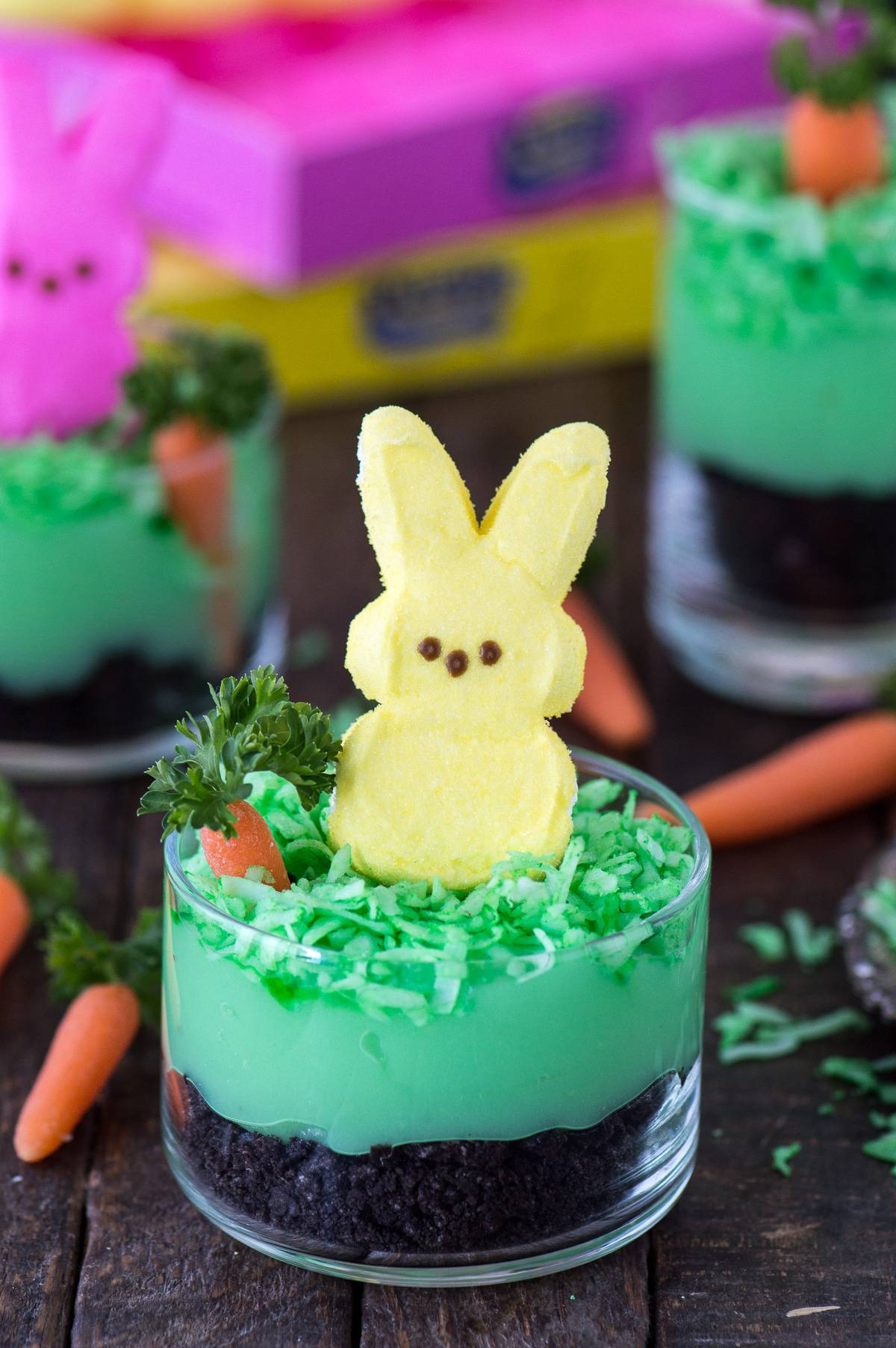 Peeps bunny pudding dirt cups with oreos, pudding, coconut, a mini carrot and a peep in a glass dessert bowl