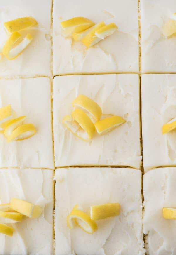 lemon cake with white frosting and lemon peels cut into pieces