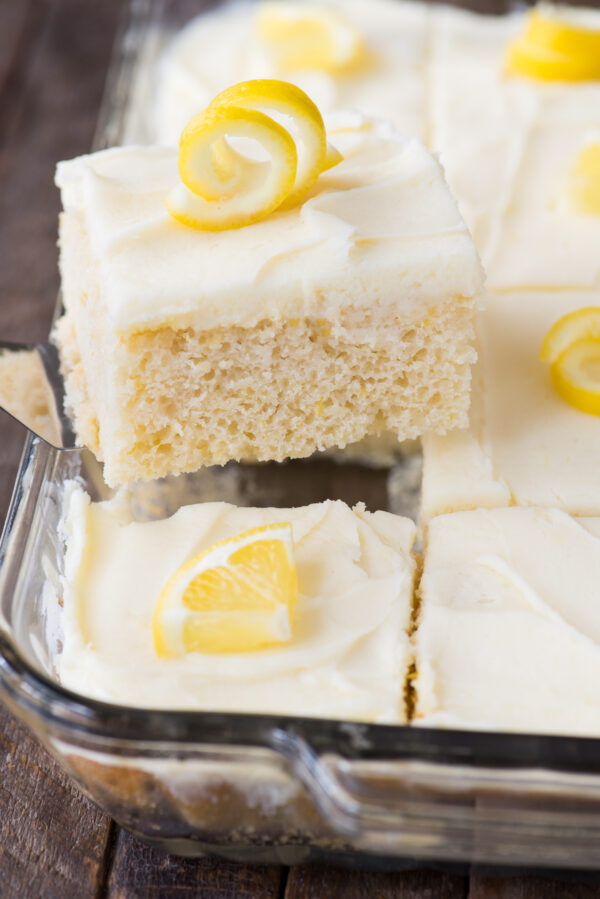 piece of lemon cake with white frosting and lemon peel on top on metal spatula