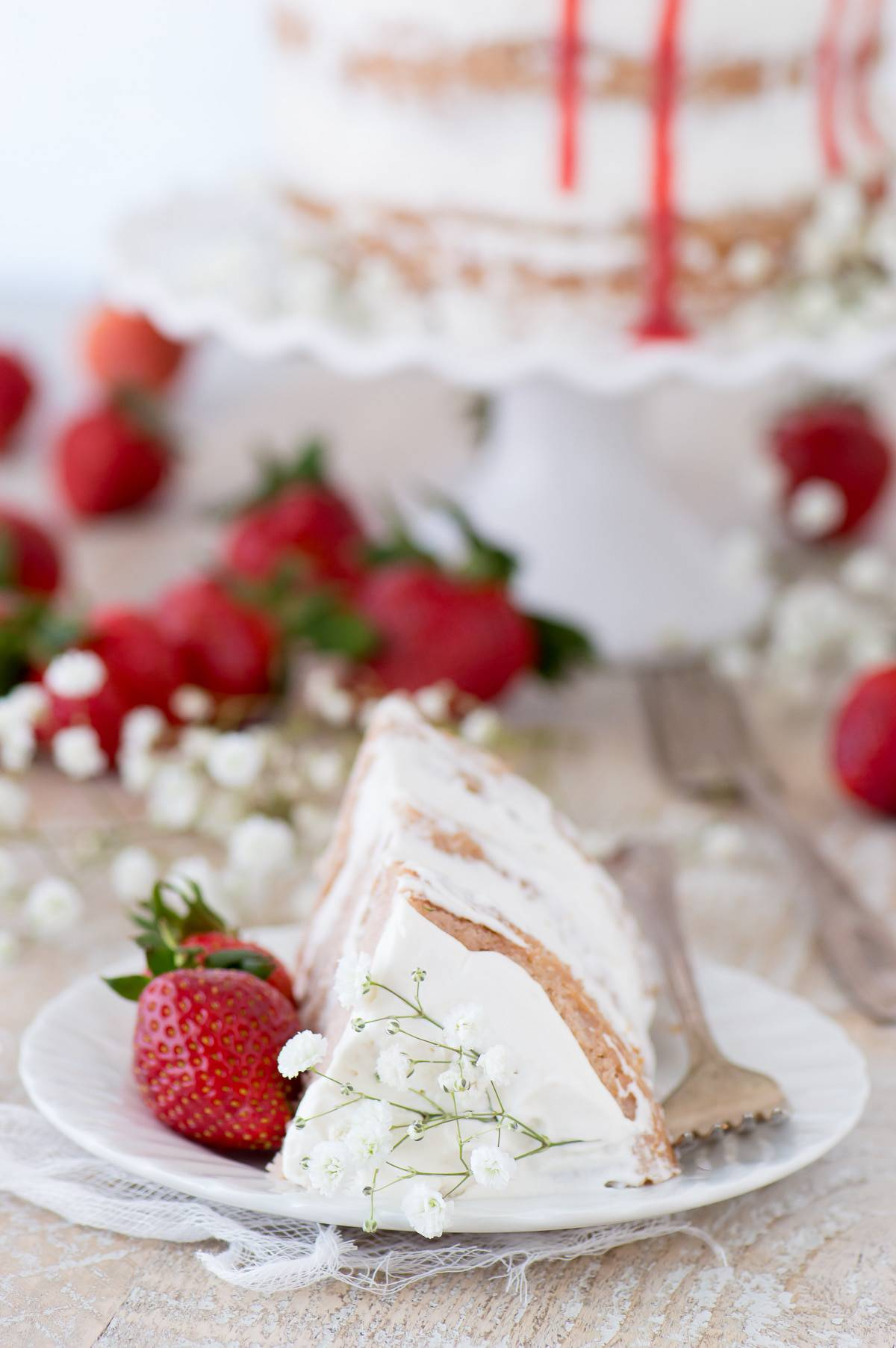 This strawberry naked cake is made with fresh pureed strawberries and is paired with homemade sweet cream whipped cream! Like a strawberries and cream cake!