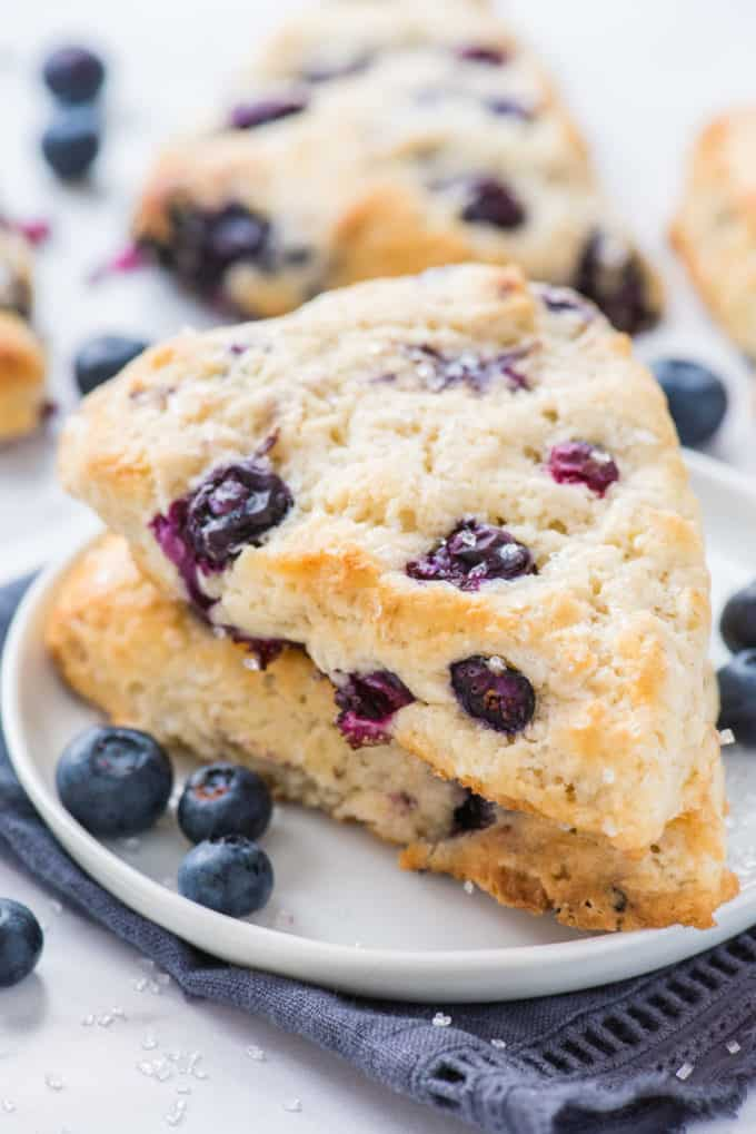 two blueberry scones stacked on each other on white plate with blue napkin