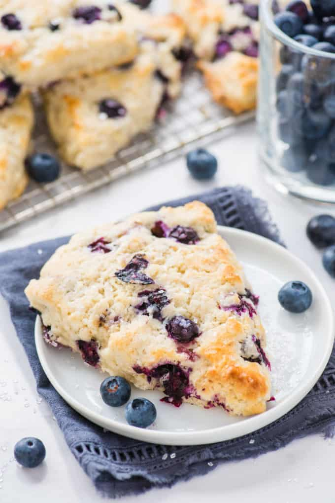 blueberry scone on white plate and blue napkin