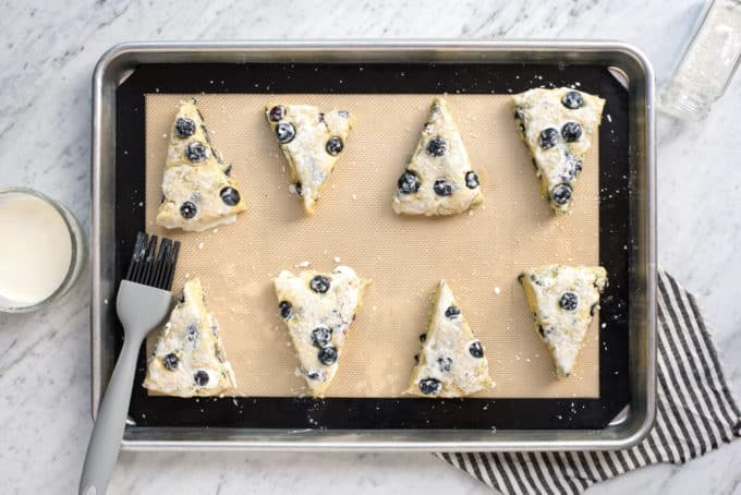 eight blueberry scones with heavy cream wash on silicone baking mat