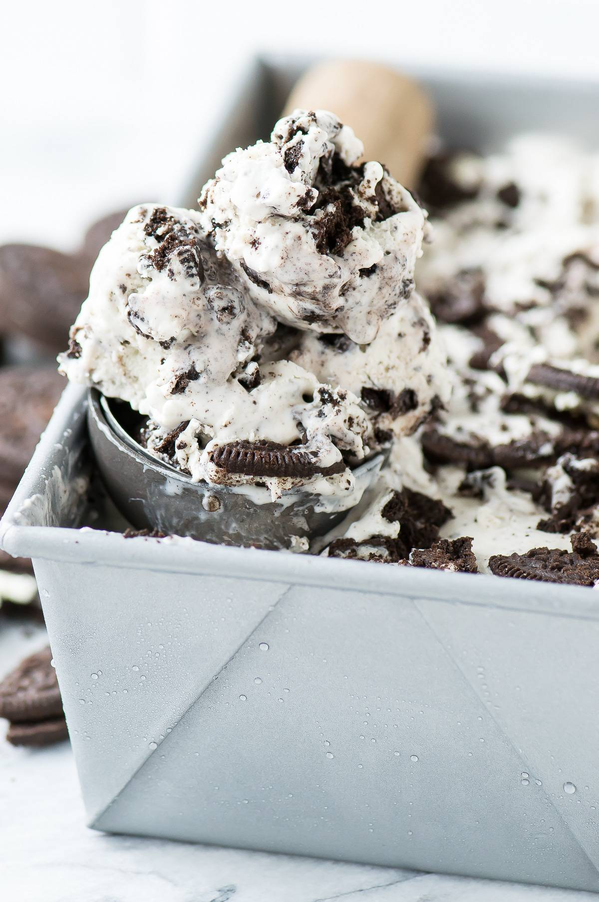 Scooping 3 Ingredient Oreo Ice Cream from a cake pan.