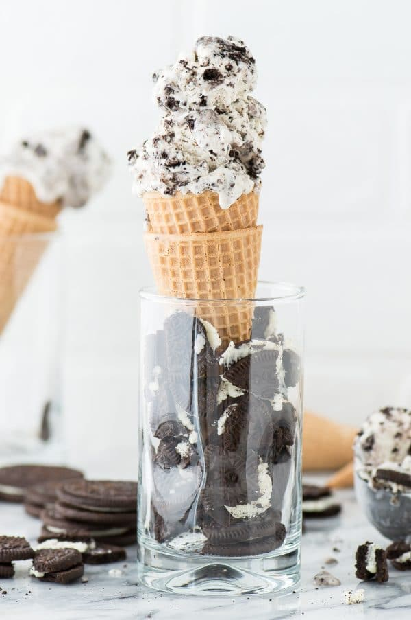 3 Ingredient Oreo Ice Cream in two waffle cones inside of a glass full of broken oreos.