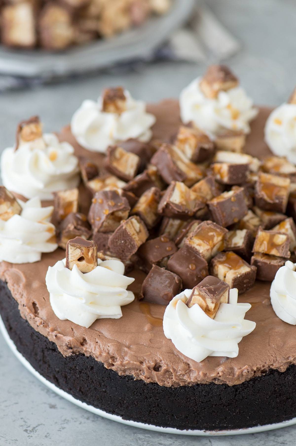 Hot Mess Nutella Snickers Pie - a no bake pie with an oreo crust, nutella cheesecake filling, topped with snickers pieces! #beyondfrostingcookbook