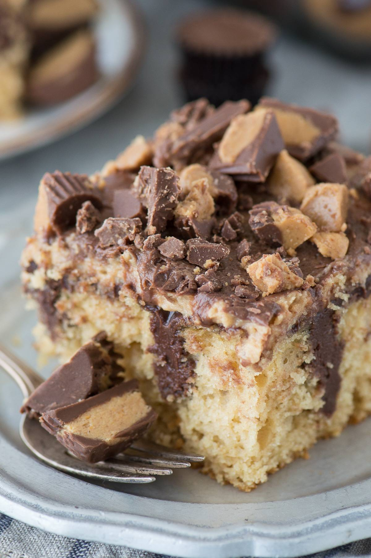 slice of reese's poke cake with chopped reese's cups on silver metal plate