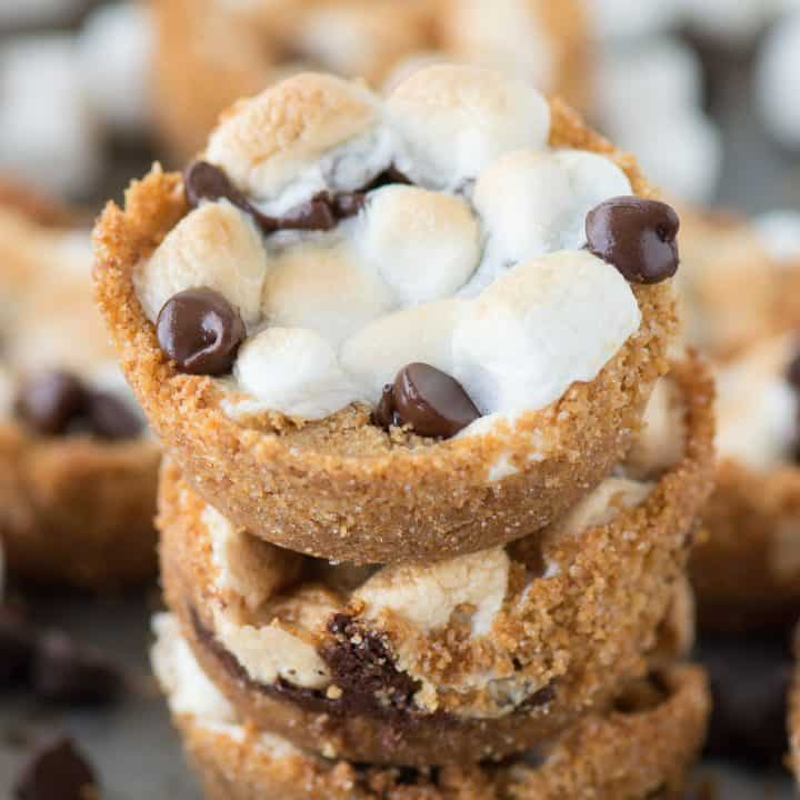 Three stacked 5 ingredient indoor S'mores Cups surrounded by other delicious s'mores cups on a baking dish.