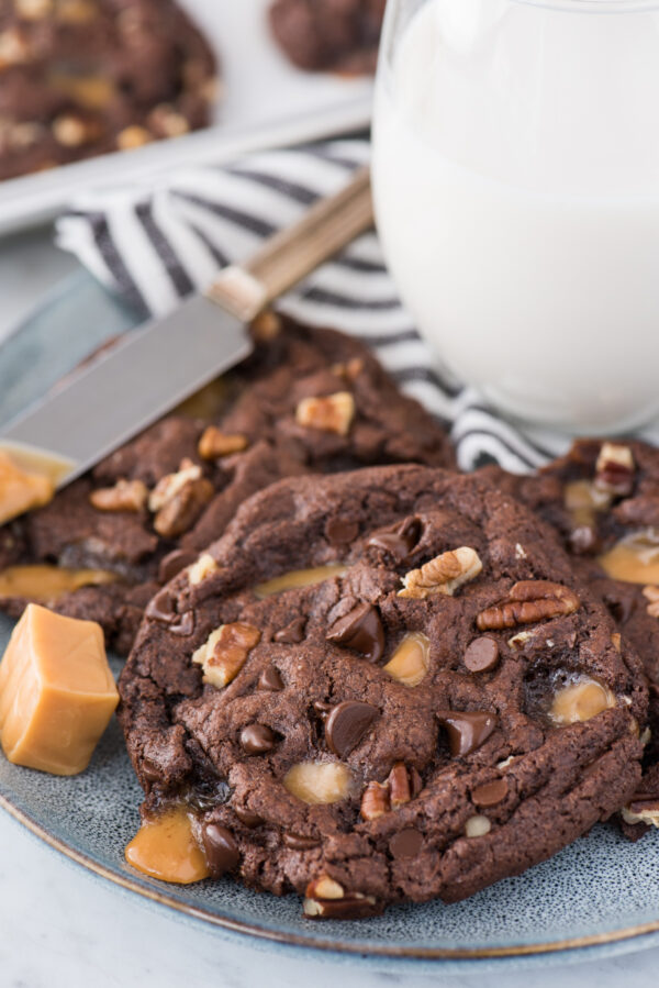 chocolate turtle cookies with caramel, pecans and chocolate chips on blue plate with glass of milk in background