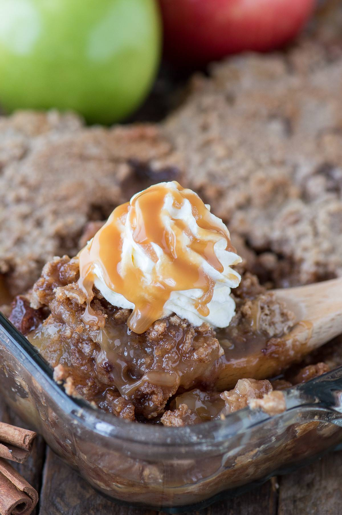 scoop of apple dump cake with whipped cream and caramel drizzle on wooden spatula