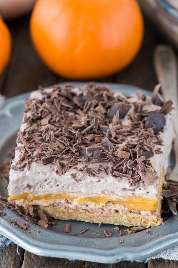 The BEST pumpkin dessert! A chocolate pumpkin dessert lasagna with 4 amazing layers. Featuring graham cracker crust, chocolate cheesecake, a pumpkin pudding layer, and homemade chocolate whipped cream!