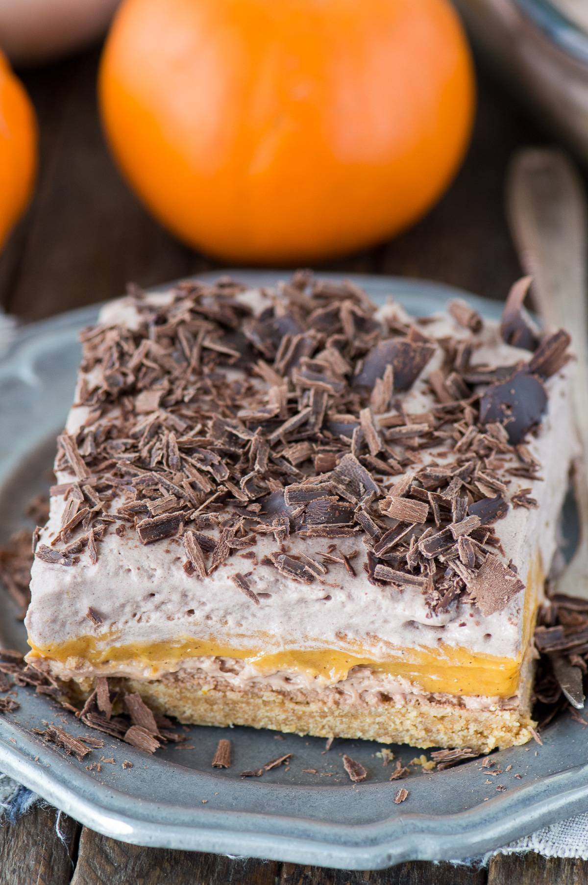 The BEST pumpkin dessert! A chocolate pumpkin dessert lasagna with 4 amazing layers. Featuring graham cracker crust, chocolate cheesecake, a pumpkin pudding layer, and homemade chocolate whipped cream!