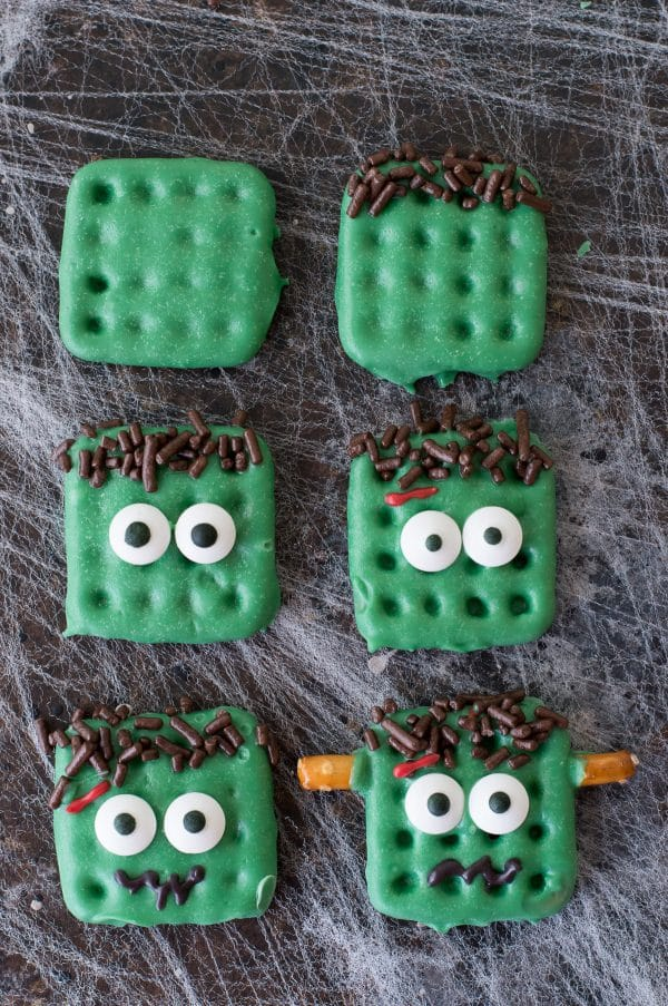 step by step how to make frankenstein treats made out of square waffle pretzels dipped in green chocolate with decorative embellishments on dark background