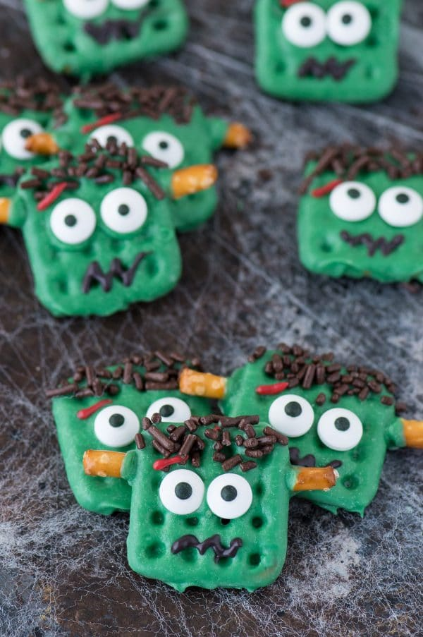 frankenstein treats made out of square waffle pretzels dipped in green chocolate with decorative embellishments on dark background