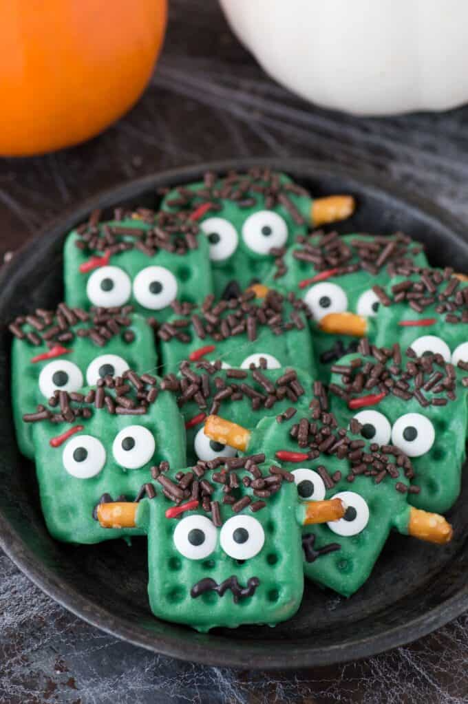 frankenstein treats made out of square waffle pretzels dipped in green chocolate with decorative embellishments on dark plate on dark background