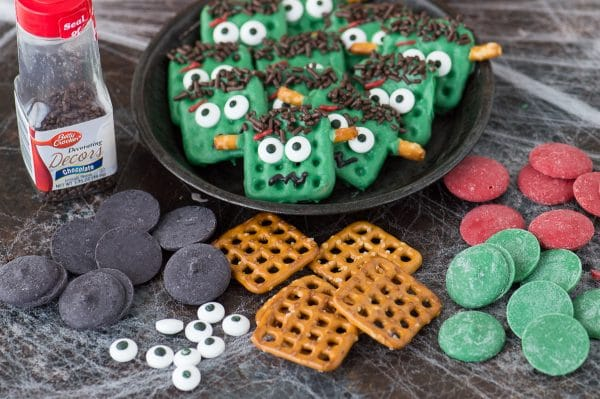 ingredients to make frankenstein pretzels including black, red and green candy melts, pretzels, candy eye balls and brown sprinkles displayed on dark background