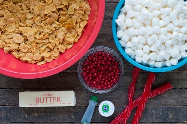 corn flakes in red bowl, marshmallows in blue bowl, red m&ms in clear bowl, stick of butter, green food coloring and twizzler's pull n peels on wood background