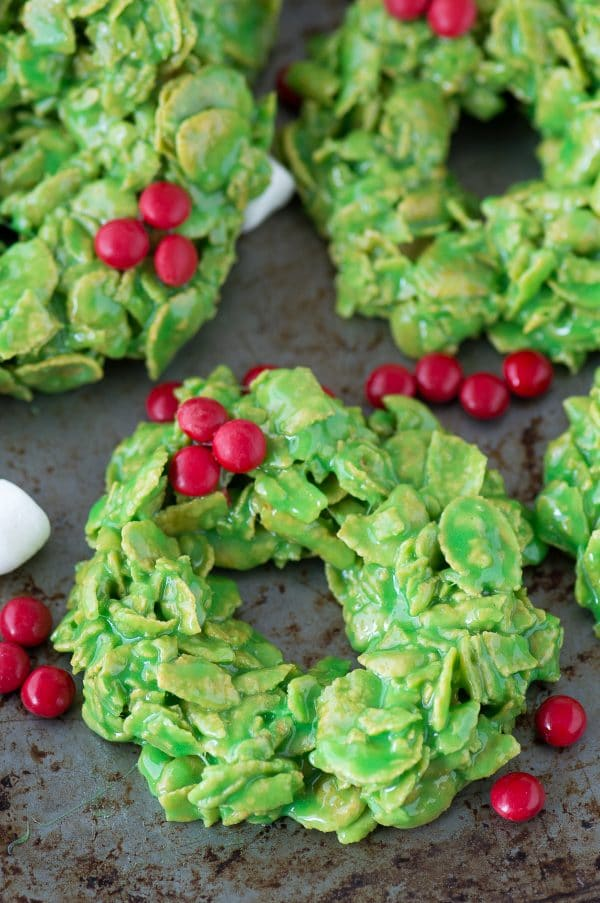 green christmas wreath cookies made with corn flakes and red mms on metal surface