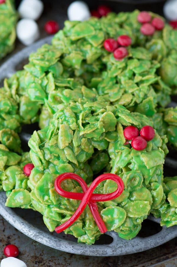 green christmas wreath cookies made with corn flakes with edible twizzlers bow on metal surface