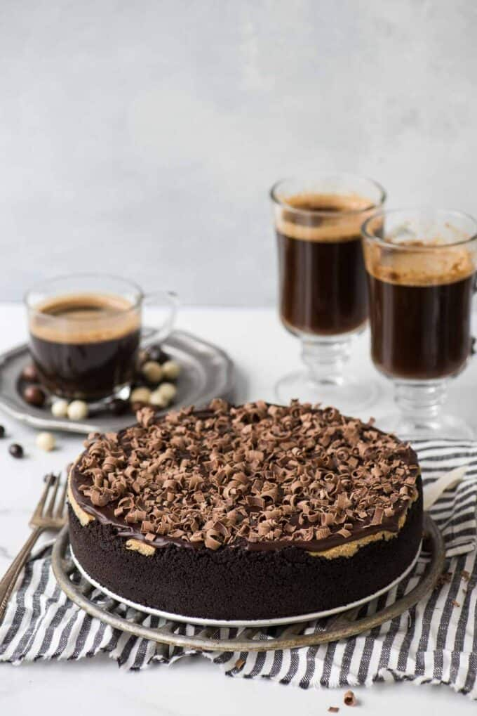 espresso cheesecake on metal stand on striped towel with coffee cups in the background