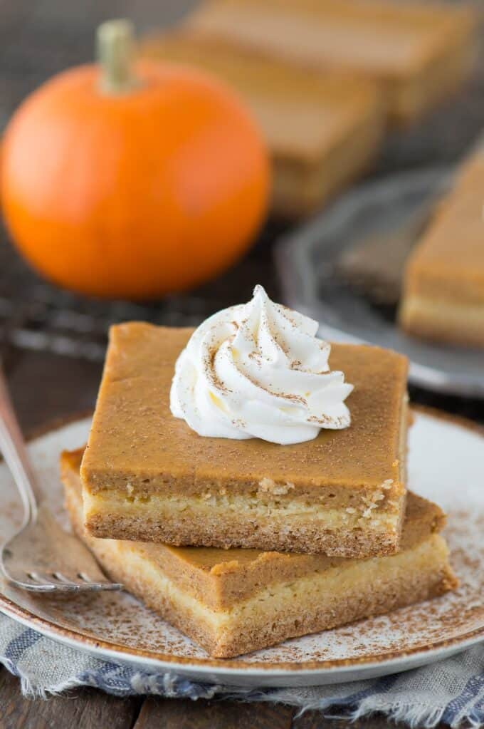 2 pumpkin pie bars stacked on top of each other on white plate with dollop of whipped cream on top