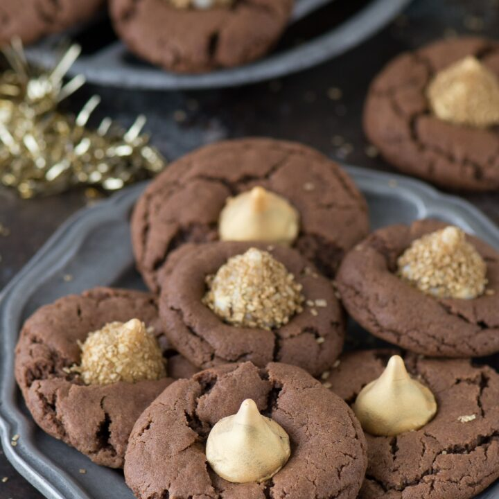 These Midnight Kiss Cookies are the best New Year's Eve cookie! There are a spin on everyone's favorite peanut butter blossoms, with a chocolate cookie base and gold hershey's kisses!