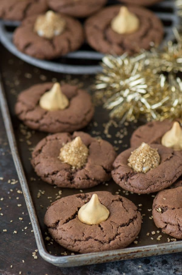 These Midnight Kiss Cookies are the best New Year's Eve cookie! They are a spin on everyone's favorite peanut butter blossoms, with a chocolate cookie base and gold hershey's kisses!