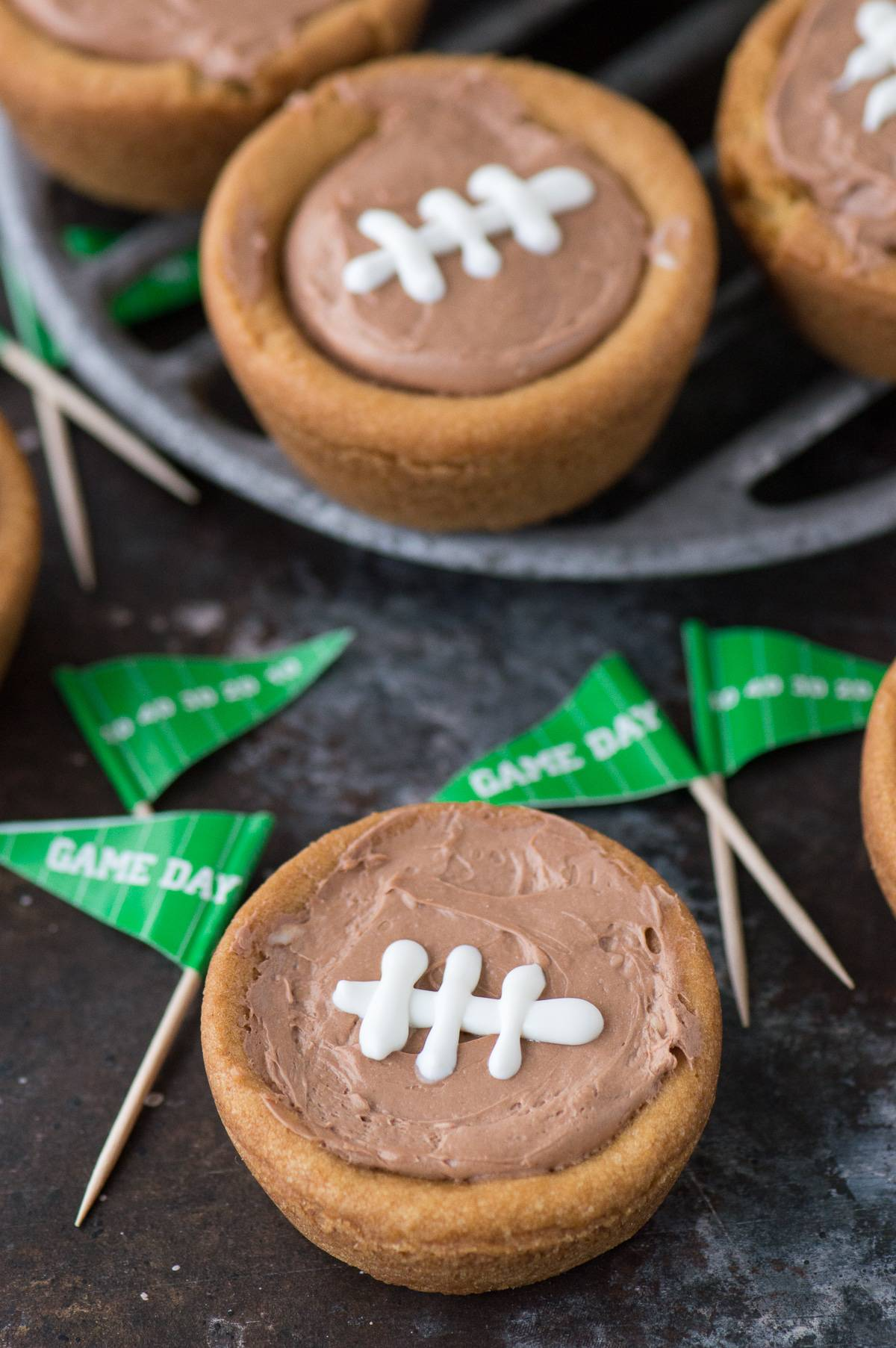 A fun game day dessert - cheesecake sugar cookie football cups! A sugar cookie cup filled with no bake chocolate cheesecake topped with royal icing football stitches!