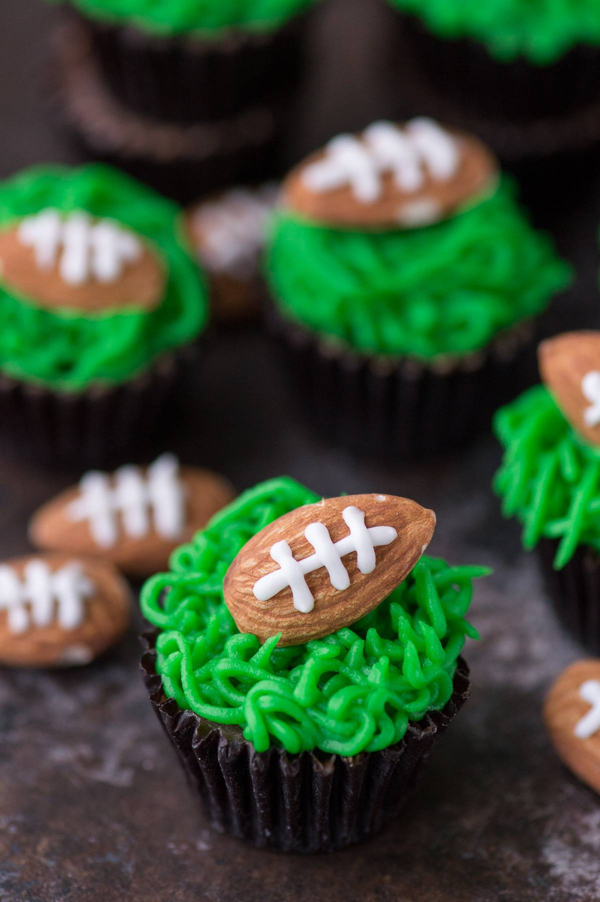 These reese's peanut butter football cups are the easiest game treat! You need peanut butter cups, green frosting and football almonds!