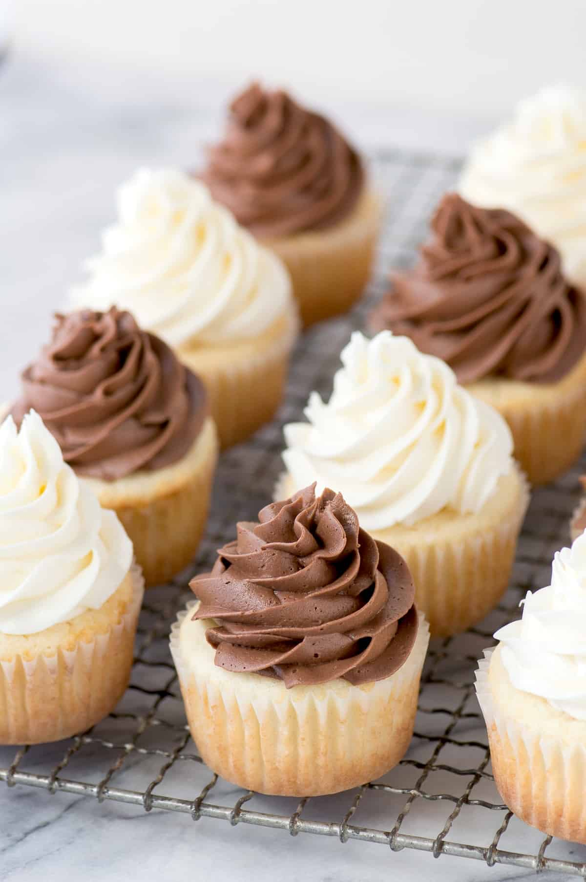 vanilla cupcakes with chocolate and white frosting on metal cooling rack on marble background
