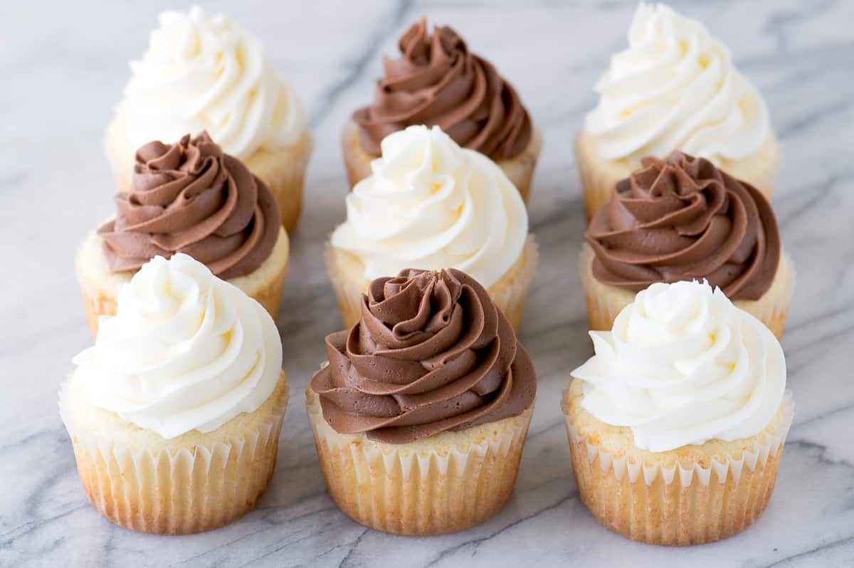 9 vanilla cupcakes with chocolate and white frosting on marble background
