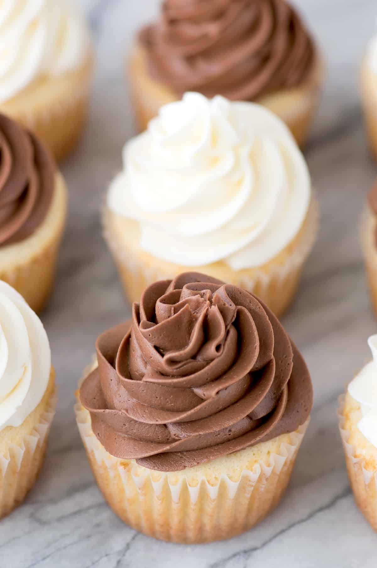 vanilla cupcake with chocolate frosting on marble background