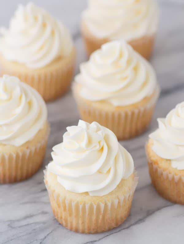 white cupcakes with vanilla frosting on marble counter top